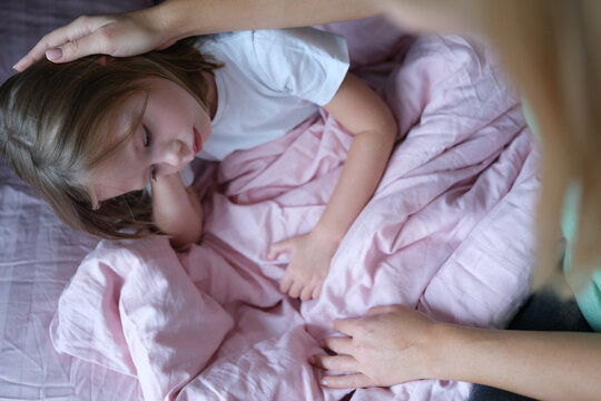 Mother stroking head of little sad girl lying in bed