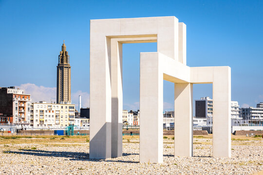 Le Havre, France - June 7, 2021: The monumental sculpture UP#3 by Sabina Lang and Daniel Baumann, installed permanently on the beach since July 2018, and the lantern tower of St. Joseph's church.