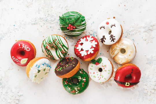 Homemade Glazed Christmas Donuts. Assorted homemade glazed donuts with sprinkles on white festive background. Top view, blank space