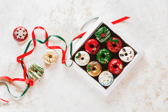 Colorful doughnuts in a gift box and beside. Christmas  Doughnuts with sugar icing  as a gift. Top view, blank space