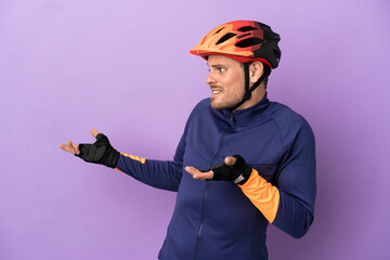 Fototapeta Young Brazilian cyclist man isolated on purple background with surprise expression while looking side obraz