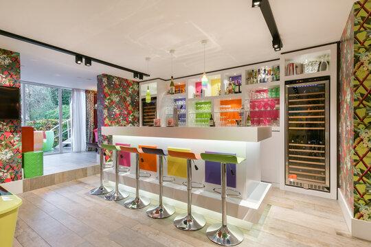 Bright and colorful private contemporary home bar. Luxury design