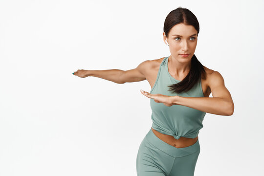 Motion shot of confident sportswoman stretching arms, looking at goal determined, standing in activewear against white background
