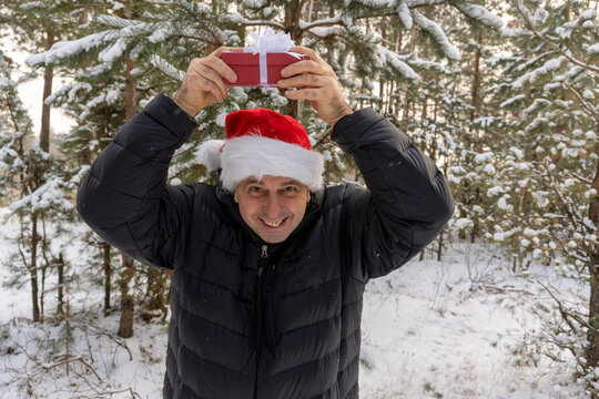 a man in a santa hat with a christmas present in the winter in the forest
