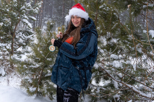 young woman in santa hat with christmas ball in winter in forest