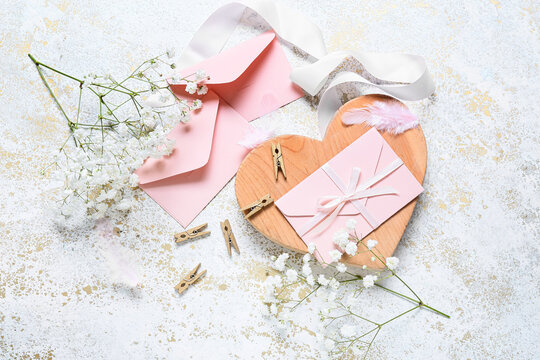 Envelopes with flowers and clothespins on white background