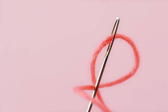 Close-up of sewing needle eye with pink thread