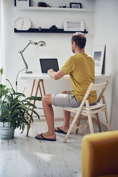 Adult caucasian man working on a laptop at home.