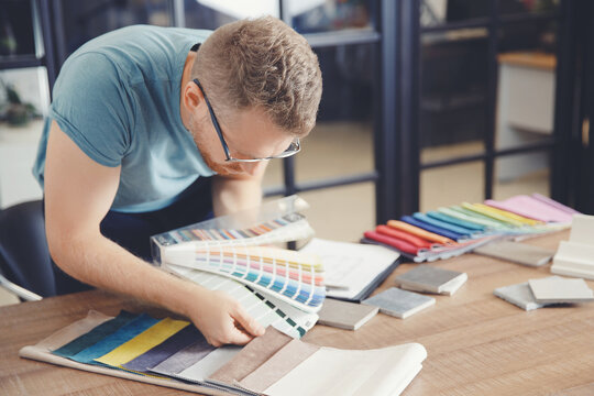 Man designer selects color of curtains and upholstery of upholstered furniture, Author supervision of design project