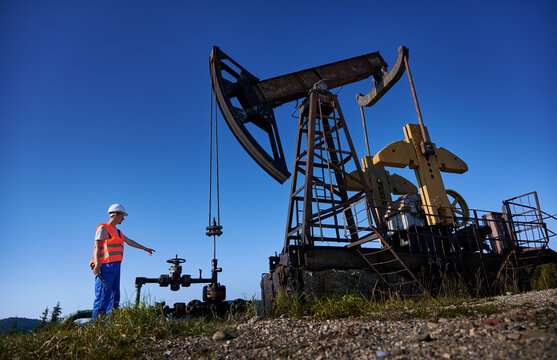 Male worker in work vest holding industrial wrench and pointing finger at petroleum pump jack while working in oil field. Petroleum engineer standing near oil pump rocker-machine under blue sky.