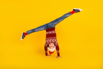 Fototapeta Full length photo of small positive girl flexible upside down christmas holiday isolated on yellow color background obraz