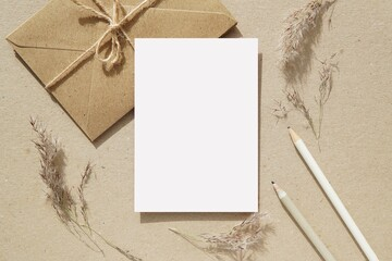 Fototapeta Letter, notecard, greeting card, postcard mockup for design presentation, envelopes, pencils, pampas grass, neutral colors flat lay composition with blank paper sheet. obraz