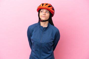 Fototapeta Teenager cyclist girl isolated on pink background and looking up obraz