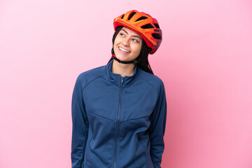 Fototapeta Teenager cyclist girl isolated on pink background looking to the side and smiling obraz