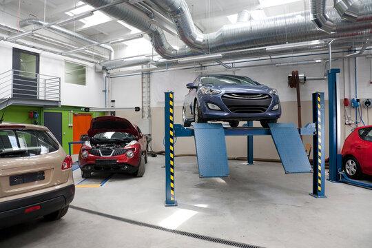 Cars in a large repair workshop or garage.