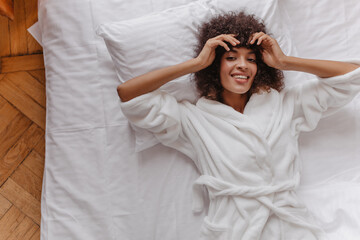 Fototapeta excited young woman in pajamas laughing lying in white bed. spectacular dark-haired girl in warm robe posing on pillow. curly brown-haired girl has fun in morning. obraz
