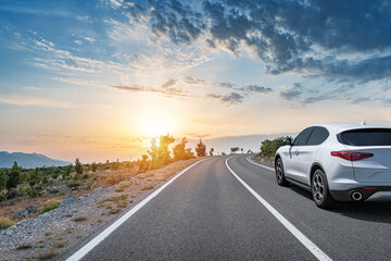 Obraz White car on a scenic road. Car on the road surrounded by a magnificent natural landscape. - fototapety do salonu