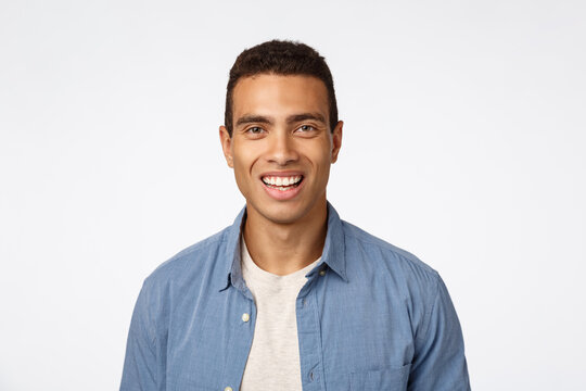 Cheerful, friendly handsome young tanned man in blue shirt over t-shirt, laughing, smiling happy as looking camera with enthusiastic, amused expression, promote something funny and joyful