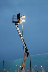 Fototapeta Człowiek w koszu podnośnika na wyskokości pracuje przy oświetleniu obraz