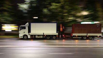 Obraz Duży samochód ciężarowy w drodze z dostawą  nocą w mieście. - fototapety do salonu