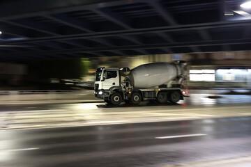 Obraz Duży samochód ciężarowy betoniarka w drodze na budowę nocą w mieście.  - fototapety do salonu