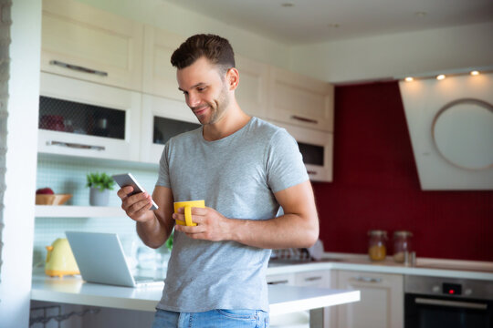 Handsome confident modern man in gray t-shirt stands with phone in hands and drinks coffee from the yellow cup on the kitchen at home