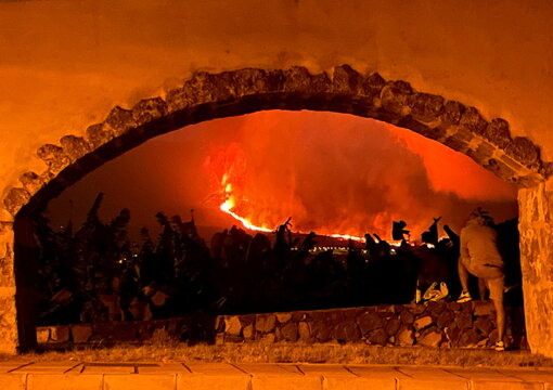 A man looks at the lava and smoke rise following the eruption of a volcano on the Island of La Palma