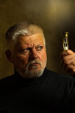 Porträt von einem älteren Mann mit Bart, er blickt skeptisch auf eine Sanduhr