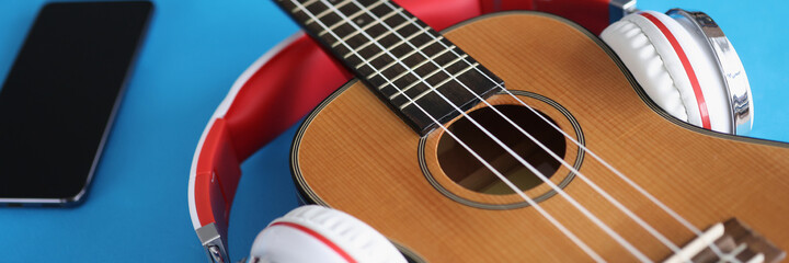 Headphones are putting on acoustic guitar on blue background closeup