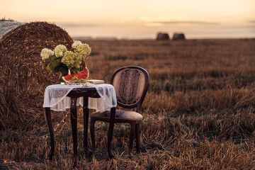 Fototapeta Autumn still life on a field with haystacks. Sunset. A table with a chair, a watermelon and flowers on the table. obraz