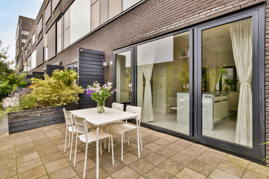 Terrace with flower bouquet on table against urban house