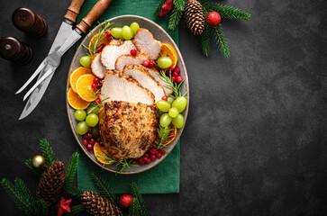 Fototapeta Christmas turkey dinner. Christmas turkey with decorations on black background, top view. obraz