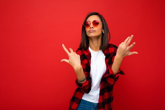 Attractive positive amusing funny young brunette woman in casual white t-shirt for mockup, stylish red check shirt and trendy red sunglasses isolated on red background with copy space