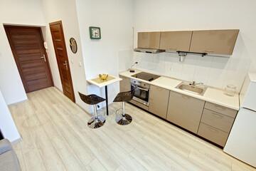 Fototapeta Beżowy pokój z kuchnią - kawalerka obraz