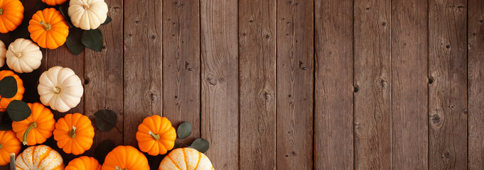 Fototapeta Fall corner border of pumpkins and eucalyptus leaves against a rustic dark wood banner background. Above view with copy space. obraz