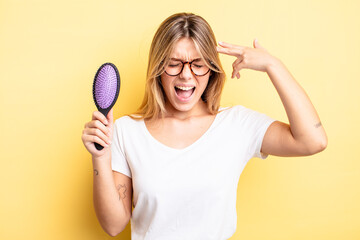 pretty blonde girl looking unhappy and stressed, suicide gesture making gun sign. hair brush concept