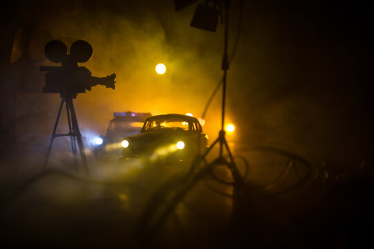 Action movie concept. Police cars and miniature movie set on dark toned background with fog. Police car chasing a car at night. Scene of crime accident.