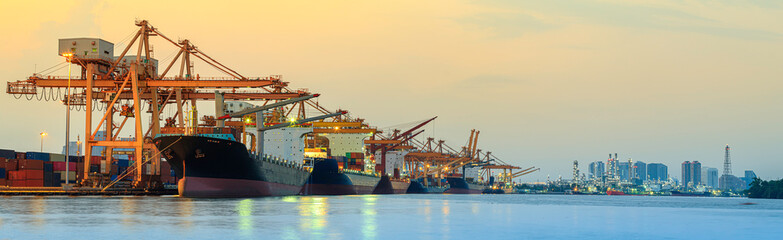 Obraz Panorama image of container cargo ship with ports crane bridge in harbor and refinery industrial at night logistics and transportation concept - fototapety do salonu