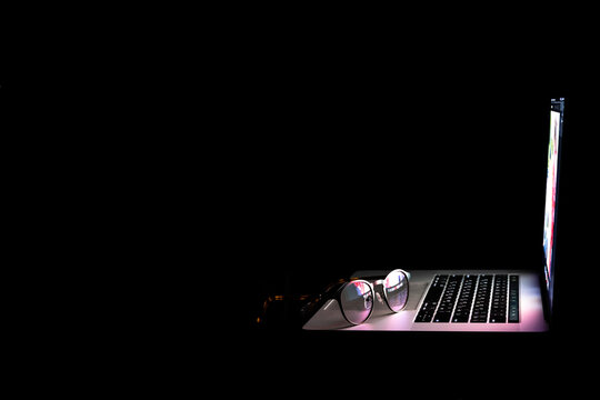Glasses near the laptop, reflect light from the screen in the dark, copy space.