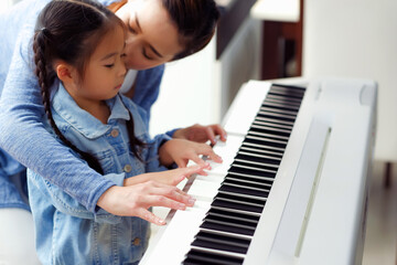 Single mom and daughter playing music with electric piano