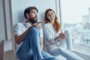 Obraz Man and woman sitting on the windowsill romance joy - fototapety do salonu