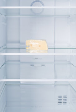 a piece of cheese, in the refrigerator on a glass shelf, on a white background