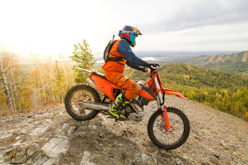 Professional motorcyclist rides in the mountains in autumn