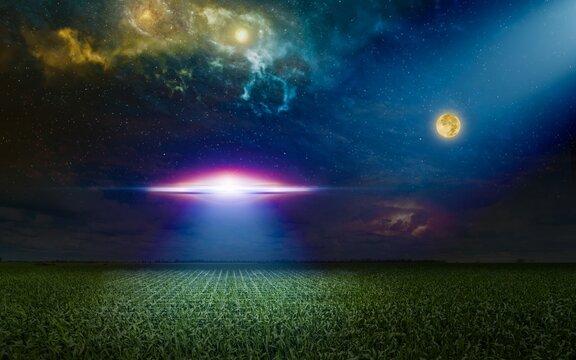 Scenic sci-fi image - ufo inspect green grass field with bright spotlight in dark night sky. Nebula and full moon in starry sky.