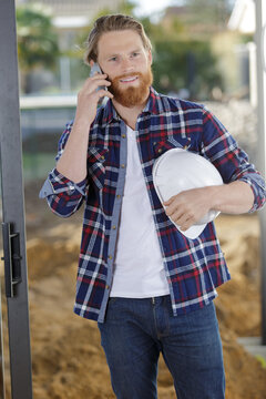 male builder uses a mobile phone