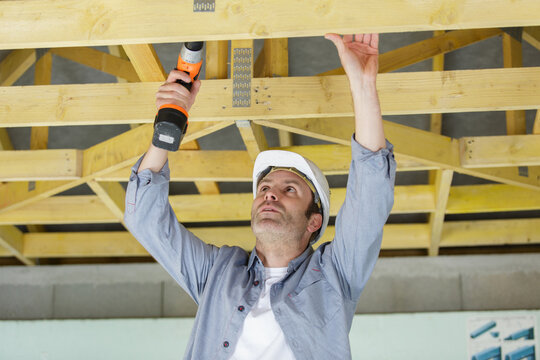 carpenter drills in a construction site