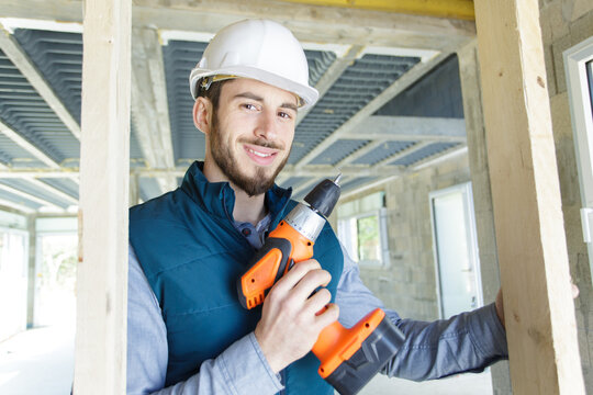 portrait of young male carpenter holding cordless power tool