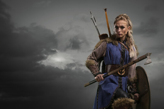Beautiful female viking woman warrior in battle with ax and bow with arrows. Amazon fantasy blonde hair sexy girl