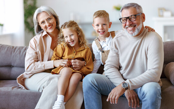 Happy family joyful little children hugging embracing with positive senior grandparents at home