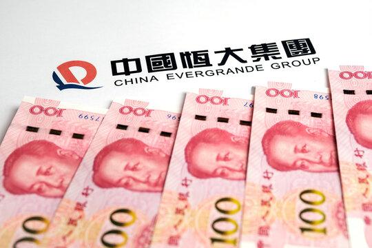 Yuan banknotes and China Evergrande Group logo. Concept. Stafford, United Kingdom, September 26, 2021.